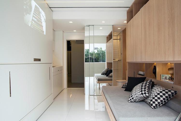 Um dos segredos para a otimização do espaço são os móveis embutidos. Os sofás - da direita (aberto) e da esquerda (fechado) - se unem para formar uma cama de casal. As portas tiveram os puxadores substituídos por recortes na madeira, o que deixa a aparência mais leve e evita enroscos e batidas durante a circulação. O projeto de arquitetura de interiores é da arquiteta Consuelo Jorge   Imagem: Raphael Briest/Divulgação