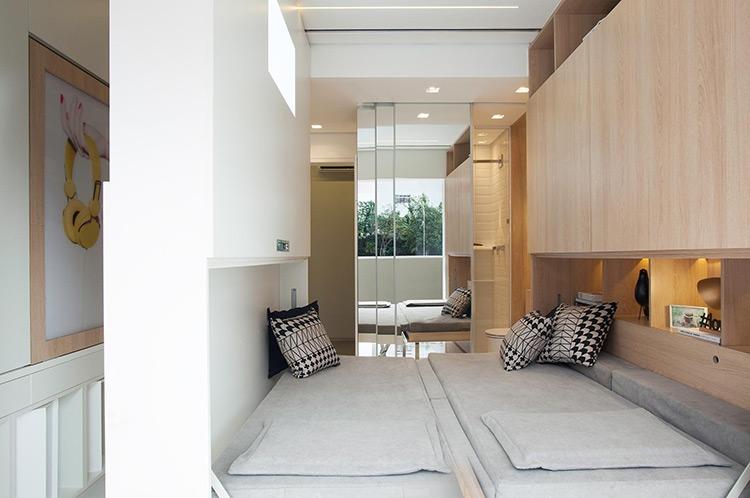 Para explorar ao máximo a área de 14 m² do apartamento, a arquiteta Consuelo Jorge idealizou uma parede/ estante de MDF (à esq.) que se movimenta a partir de trilhos fixados na laje. Conforme a posição, a divisória revela o quarto (foto), onde é possível montar uma cama de casal, ou a sala de jantar e o escritório   Imagem: Raphael Briest/Divulgação