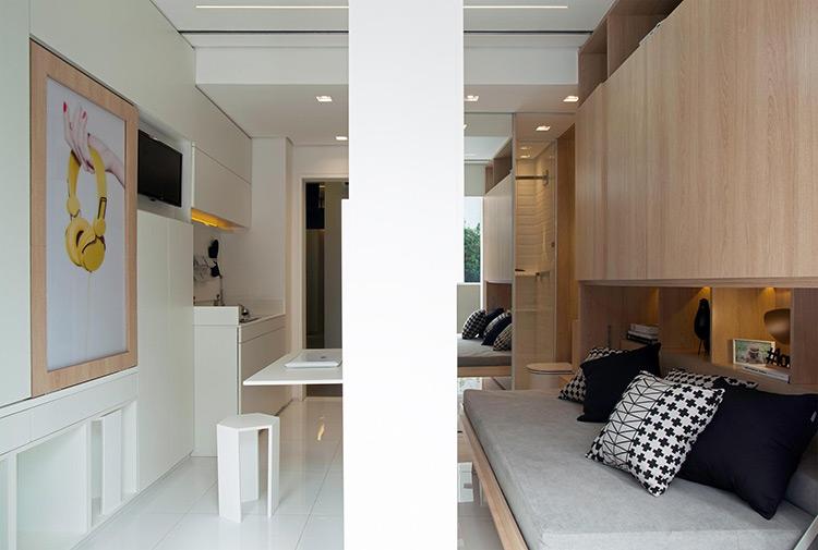 A parede de MDF (fibras de madeira compensadas) funciona como um armário com dupla face: de um lado, além de prateleiras, abriga uma cama; do outro dá suporte à bancada de trabalho. O banquinho pode ser guardado no nicho da parede, abaixo do quadro (à esq.). A arquitetura de interiores foi concebida por Consuelo Jorge   Imagem: Raphael Briest/Divulgação