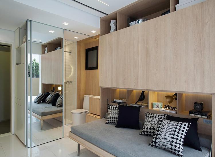 Os ambientes do pequeno apartamento são integrados, com exceção do banheiro (ao fundo), resguardado pela porta espelhada de correr. A madeira e o branco usados na decoração dão ideia de movimento visual e ajudam a delimitar os espaços no projeto do escritório Consuelo Jorge Arquitetos   Imagem: Raphael Briest/Divulgação