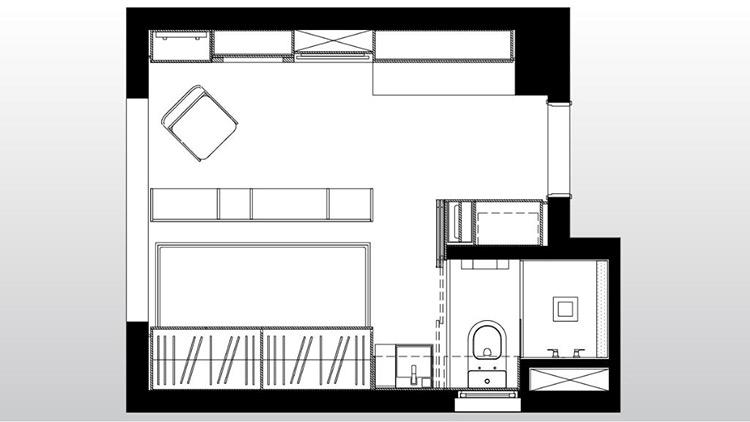 Na entrada já estão a compacta cozinha (à dir.) e a lavanderia (à esq.), ambas camufladas por armários. Para definir salas, escritório e quarto no apartamento de 14 m², a arquiteta Consuelo Jorge projetou uma parede móvel de madeira   Imagem: Raphael Briest/Divulgação