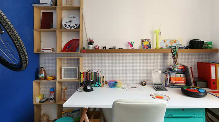 Na parede de frente para a mesa, um painel perfurado é ótimo para colocar ganchos com lembretes. Os nichos e as prateleiras de MDF cru são acessíveis e descolados. O projeto é do escritório SP Estudio, das arquitetas Fabiana Silveira e Patricia de Palma