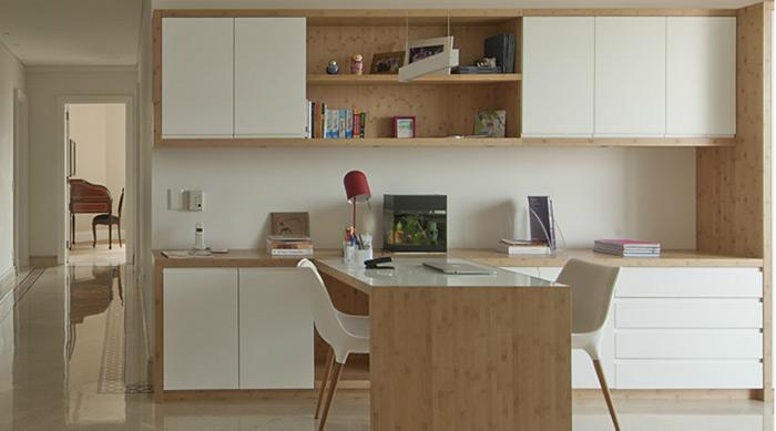 """Para quem trabalha em dupla ou tem reuniões em casa, uma mesa única é a solução. Móveis de cores neutras também são interessantes para não """"enjoar"""" no dia a dia. O projeto é do escritório Figoli-Ravecca"""