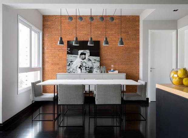 A sala de jantar tem parede revestida com tijolos Pasinato. Mesa de jantar e cadeiras da Carbono Design. O buffet foi desenhado pelo escritório Drops e executado pela REM Marcenaria. Pendentes à venda na Reka (Foto: Julia Ribeiro/Divulgação)